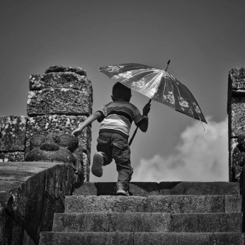 A kid runs away from the intense heat, looking for a shadow in Ratu Boku, an archaeological site in Jogjakarta.