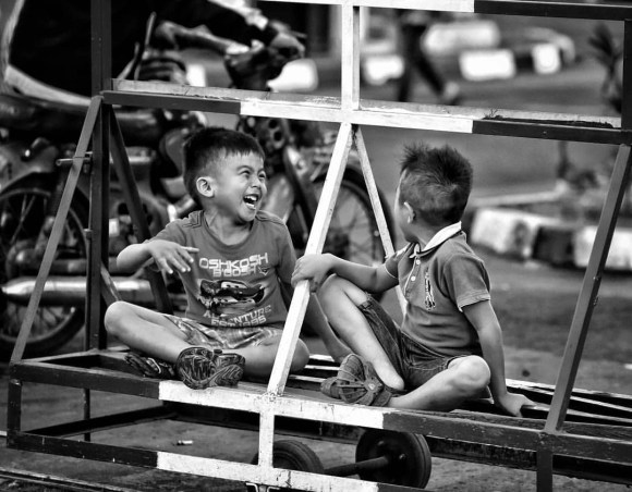 These kids were having a blast while standing on the safety mobile fence in front of Yogyakarta's main railway junction.