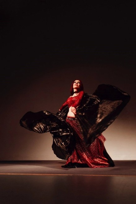 Woman dancing flamenco in a red long skirt and blouse