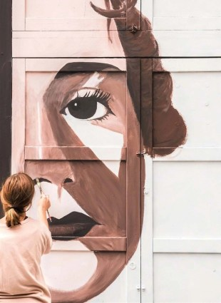 Woman painting a big mural on a Malasaña street - Offbeat Madrid things to do