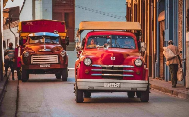 A couple of red cars in a centric Santiago de Cuba street - Unmissable stops on a Cuban road trip