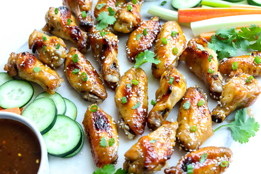 thai chicken wings on white surface with fresh veggies
