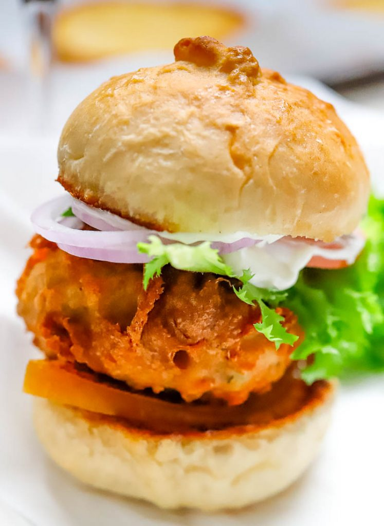 photo of a deep fried burger on a bun with lettuce and tomatoes
