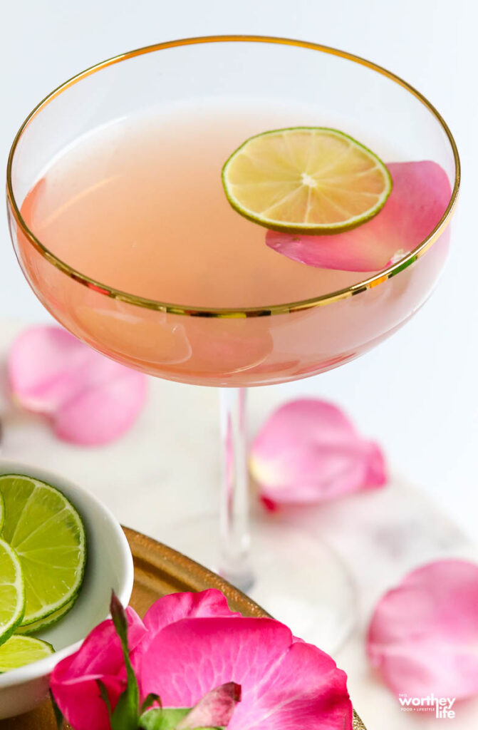 a pink gin cocktail in a couple glass garnished with a rose petal and lime