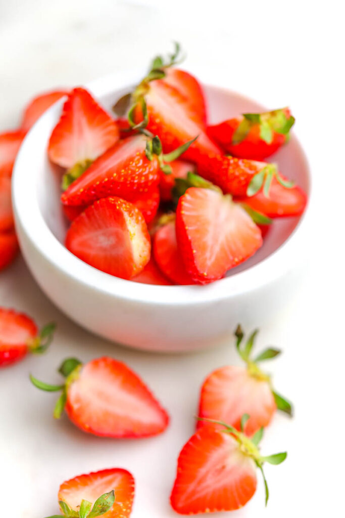 fresh strawberries cut up in a white marble bowl