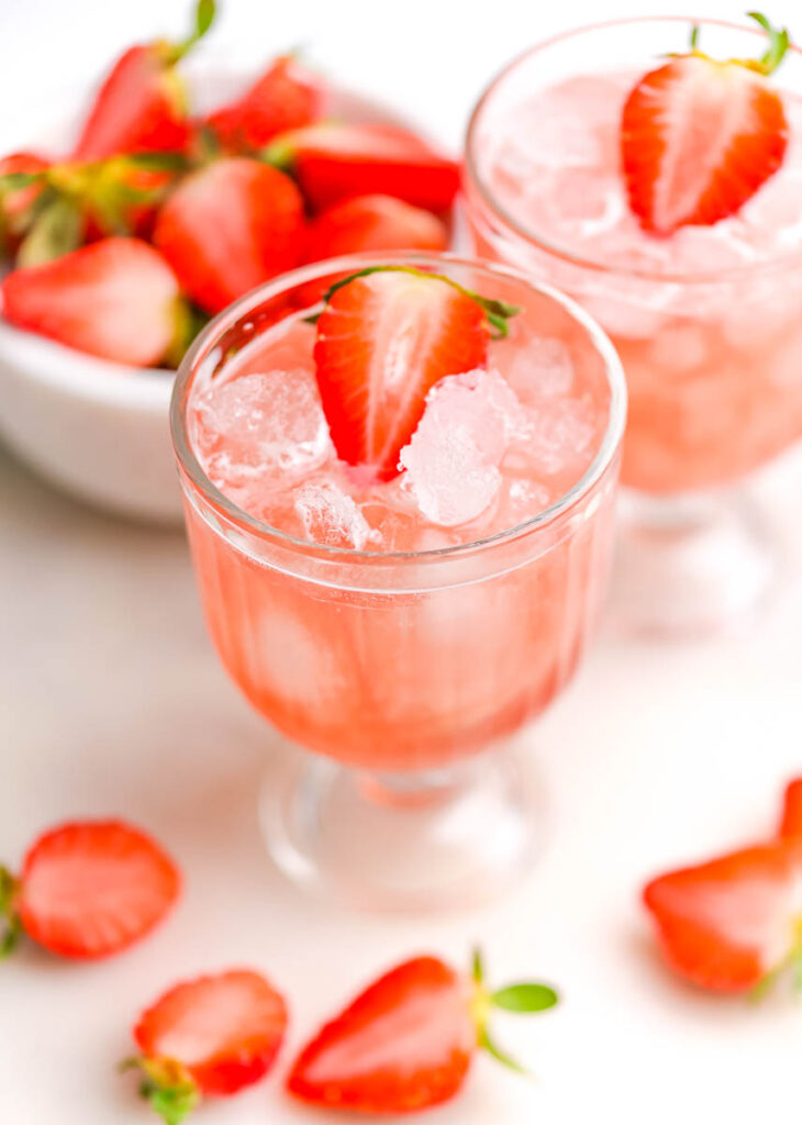 cranberry mocktail with fresh strawberries on a white background