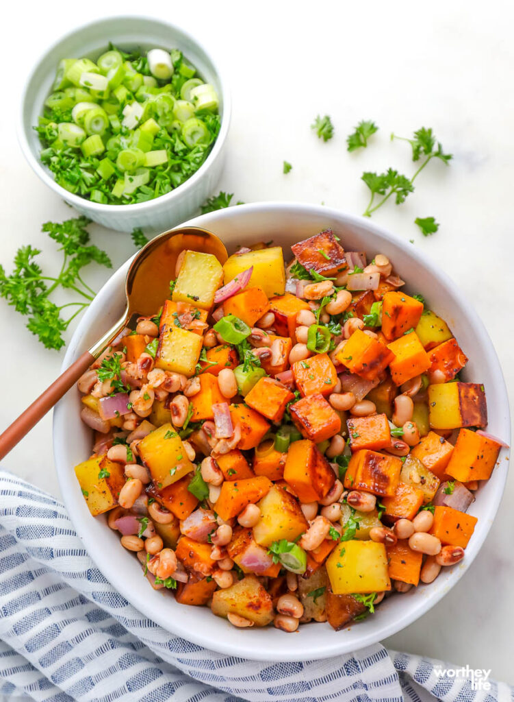 diced sweet potatoes mixed with black-eyed peas with fresh herbs in a white serving bowl