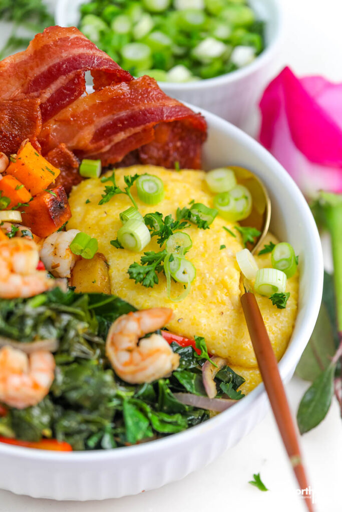 a white bowl with greens, cheesy grits, and bacon