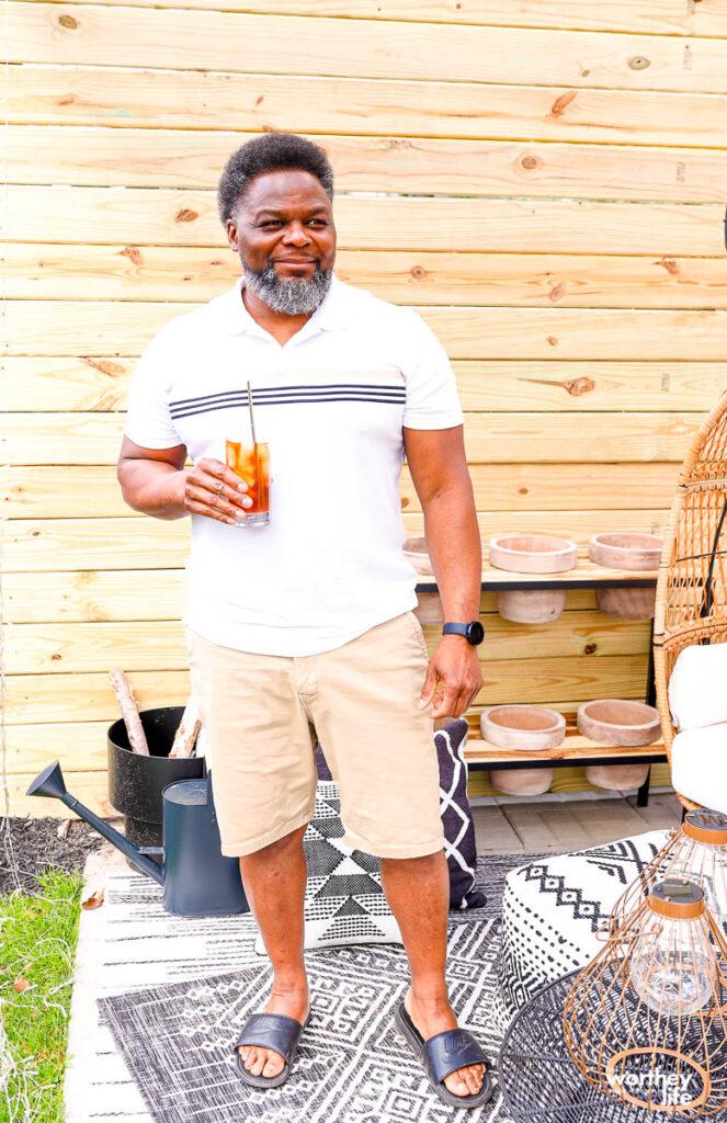 a man drinking ice tea on the patio