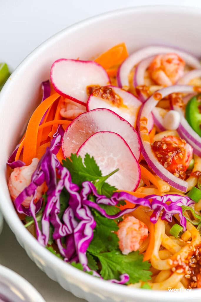 seafood soba noodle salad topped with fresh vegetables and an Asian vinaigrette