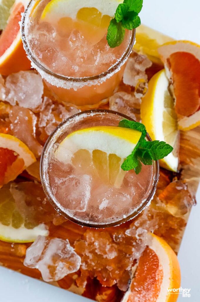 two serving of a paloma cocktail surrounded by palomas and grapefruit