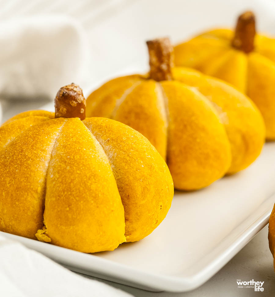pumpkin shaped dinner rolls on white plate