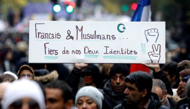 """متظاهرون يحملون لافتة كُتب عليها """"فخورون بهويتنا الفرنسيّة وبالإسلام""""، أثناء مسيرة في باريس للاحتجاج ضد الإسلاموفوبيا"""