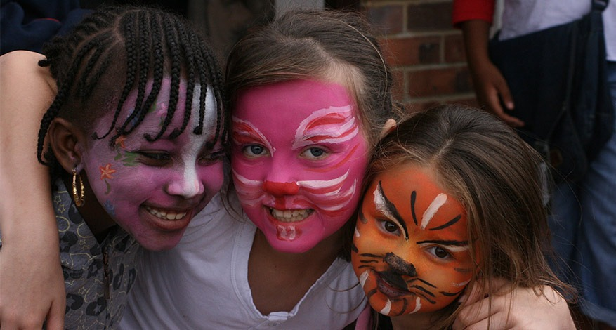 Three children have their face painted at elevating success event.