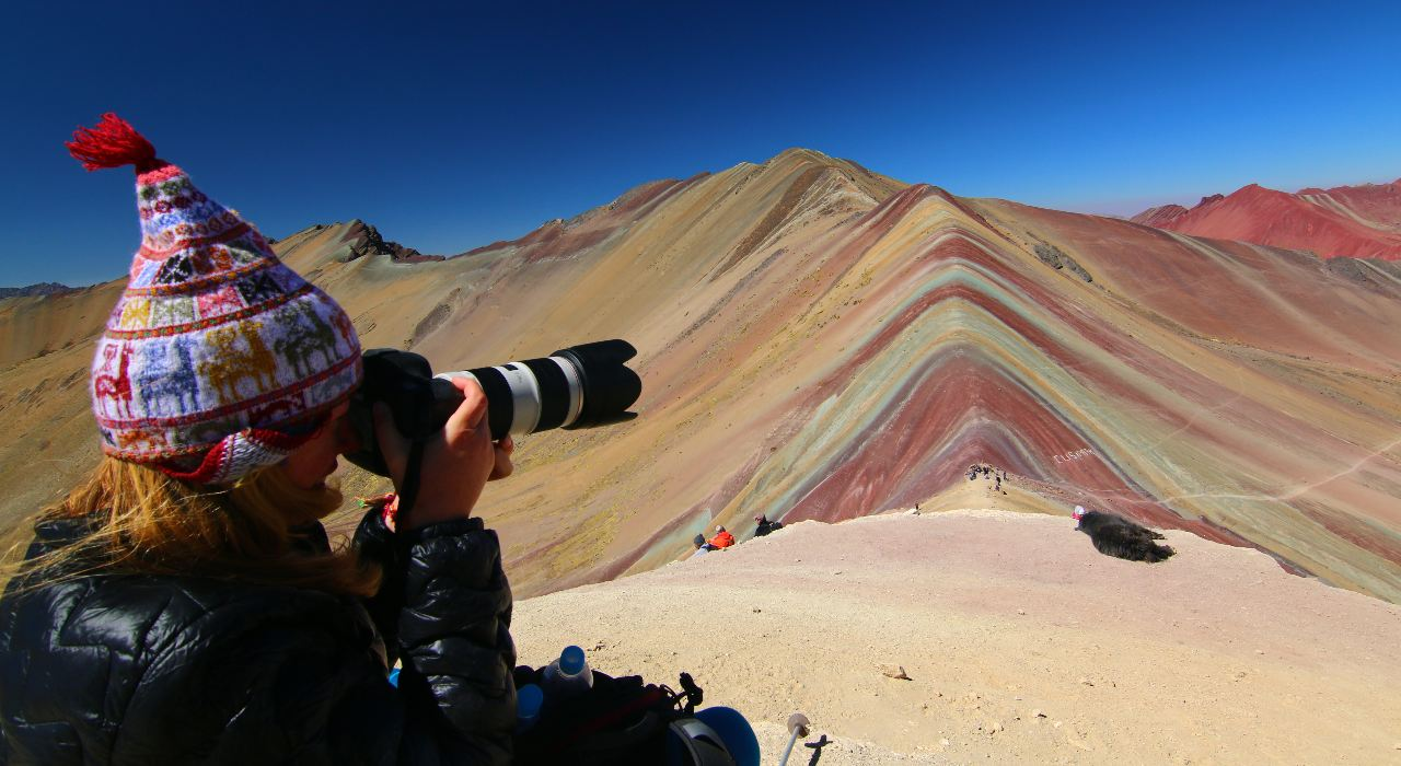A photographer at the viewpoint for Vinicunca, aka Rainbow Mountain, Peru