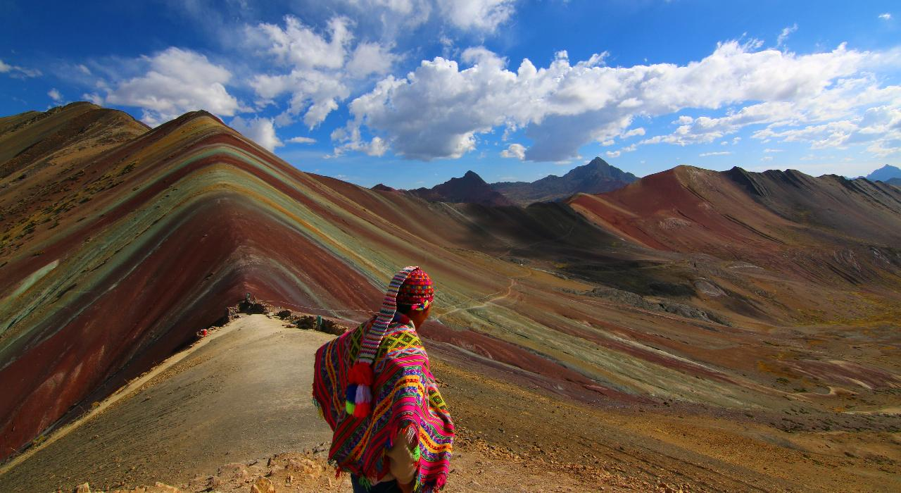 A person dressed in traditional Peruvian clothing stands with their back to the camera in front of Rainbow Mountain or Vinicunca in Peru