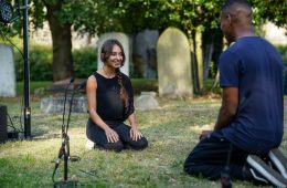 A woman is sitting on a grass patch in front of a man. They are in a graveyard.