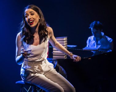 A woman wearing white sits on a stool with her hand resting on a piano. In the background, a man sits at the keys.