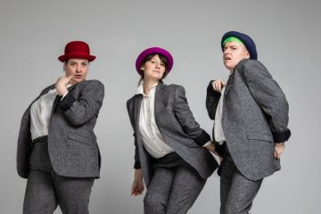Three people in matching grey suits and brightly coloured bowler hats stand against a blank grey background.