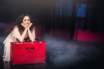 A young woman is leaning on a bright red box.