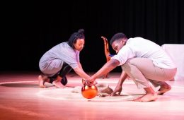 Two performers crouch on the floor — the one on the right holds an orange ball. Between them is a circle of sand.