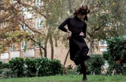A person in a long black dress dances in a garden, the building behind them obscured by trees. Their face is covered by their hair, and they are suspended in mid-jump.