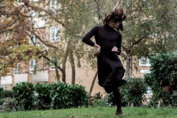 A white woman in a long black dress dances in a garden, the building behind her obscured by trees. Her face is covered by her hair, and she is suspended in mid-jump.