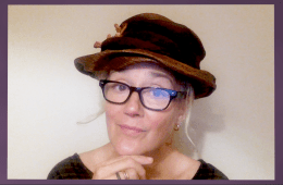 A lady wearing a brimmed hat and glasses.