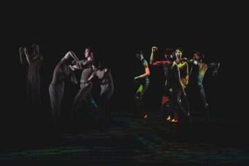 2 groups, 4 asian dancers in each. The group on the left is in a neutral light, preparing to lift one member. The group on the right is in multicoloured lights, in various poses where they're elbows are up.