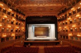 A picture of an empty, grand, proscenium arch theatre.