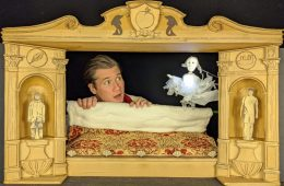 A small theatre style box, a man's head in a small bed looks at a puppet ghost