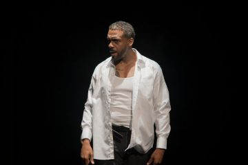 A man is standing against a black background. He is dressed in a white shirt and formal trousers.