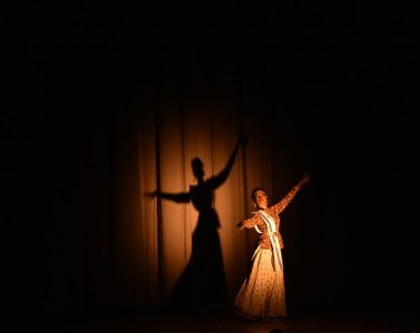 A performer stands against a backdrop with arms outstretched. They are silhouetted by a spotlight.