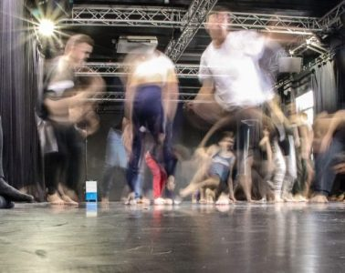 Actors in a black box rehearsal room move about, with a blurred effect added on top.