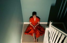 Woman sitting on the floor at the foot of the stairs