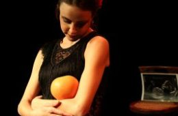 A woman cradling an orange.
