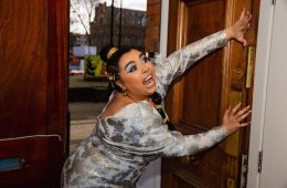 A woman wearing a bright, silver gown is bursting through a wooden door, an excited expression on her face.