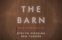 """A wooden background. Written on the background: """"The Barn"""""""