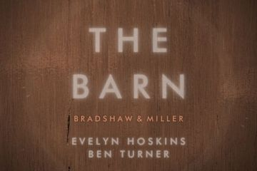 "A wooden background. Written on the background: ""The Barn"""