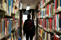 A person, cloaked in darkness, walks in between stacks of books