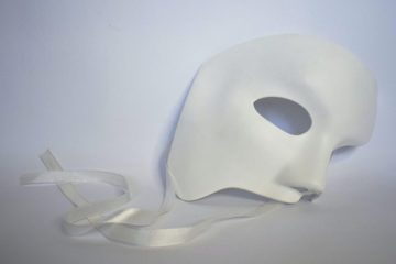 A white Phantom of the Opera-style mask lies on a white floor