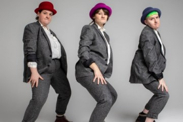 Three women in grey suits and wearing coloured hats