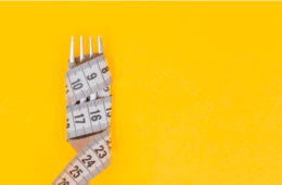 Tape measure wound around a fork on a yellow background
