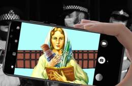 A mobile phone held by a hand. The screen of the phone shows a picture of the Virgin Mary.