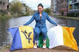 A woman in a denim jumpsuit happily sits in front of a blue, yellow, green and white flag