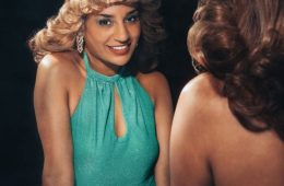 A young women, dressed in a turquoise dress which curled hair is standing in front of a mirror and looking at the camera's reflection in the mirror.