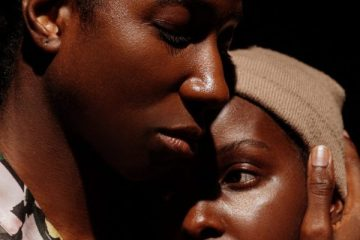 An intimate, close up portrait of two people embracing.