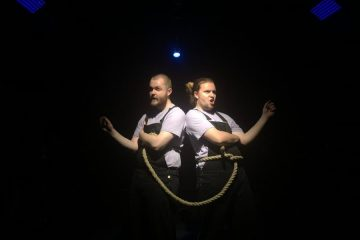Two men tied together by a rope
