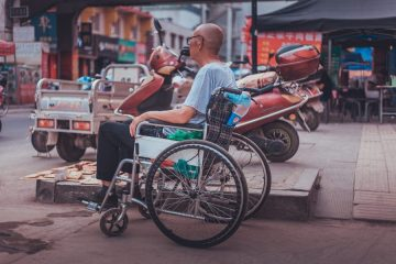 A man in a wheelchair sits in what looks like an area with chinese restaurants