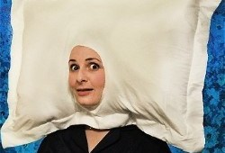 A person with a pillow over their head. the pillow has a whole for the face.